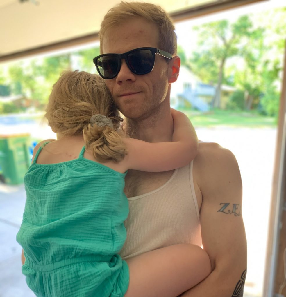 Zach West holding his kid looking really cool with sunglasses